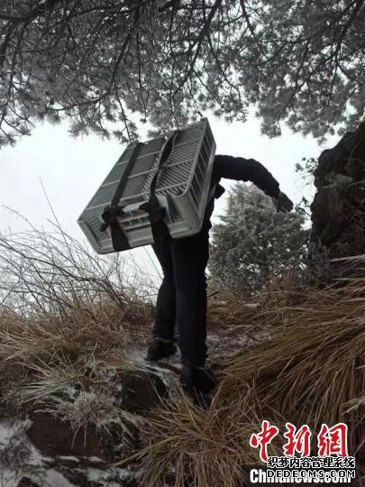 技术人员冒着风雪攀爬上陡坡 王政 摄